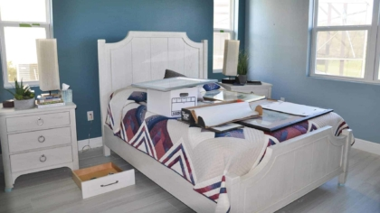 bed covered with everything from the bedroom walls & some stuff from the master bathroom